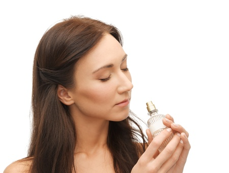 perfumer: picture of young beautiful woman smelling perfume Stock Photo