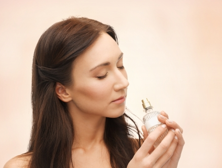 picture of young beautiful woman smelling perfume photo