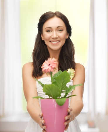 bright picture of lovely housewife with flower in pot photo