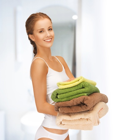 laundry pile: bright picture of lovely housewife with colorful towels
