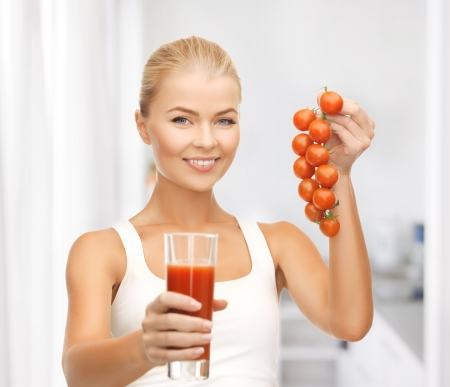 young woman holding glass of juice and tomatoes photo