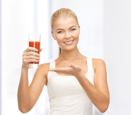 young woman holding glass of tomato juice photo