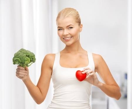 young woman holding heart symbol and broccoli Stock Photo - 19293209