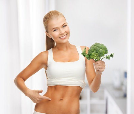 six pack: beautiful woman pointing at her abs and holding broccoli