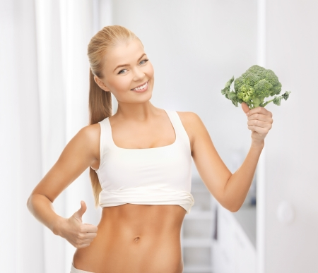 abdomens: beautiful woman pointing at her abs and holding broccoli