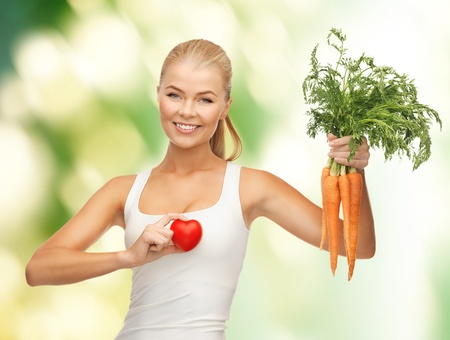lifestyle disease: young woman holding heart symbol and carrots Stock Photo