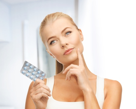 birth control: picture of thoughtful young woman with pills Stock Photo