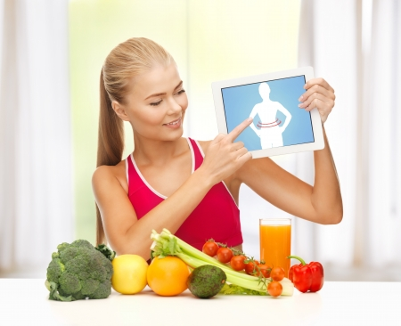 sporty woman with fruits and vegetables pointing at tablet pc photo