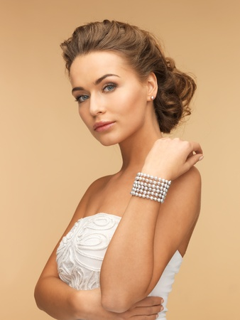 beautiful bride wearing pearl earrings and bracelet photo