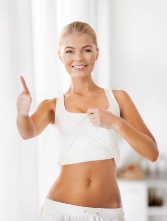 shaping: beautiful sporty woman showing thumbs up and her abs