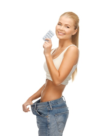 loose: woman showing big pants and pack of pills Stock Photo