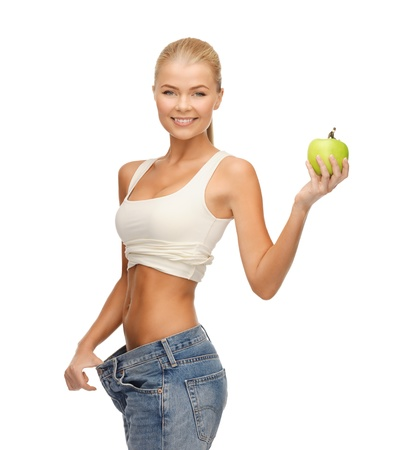 fat burning: picture of sporty woman showing big pants and apple