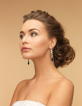 beautiful woman in white dress and diamond earrings photo