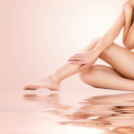 picture of healthy naked woman legs over beige background photo