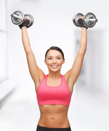 shaping: picture of young sporty woman with heavy steel dumbbells Stock Photo