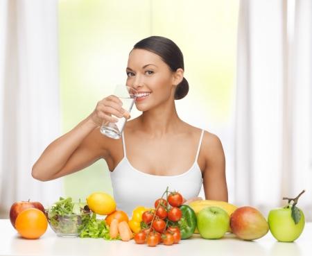 schöne Frau mit gesunden Lebensmitteln und Wasser