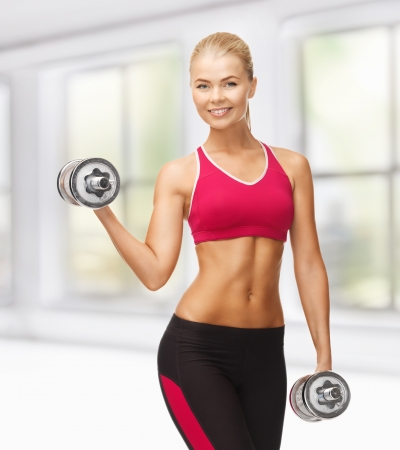 picture of young sporty woman with heavy steel dumbbells Stock Photo