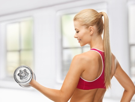 close up of young sporty woman with heavy steel dumbbell Stock Photo - 19347260
