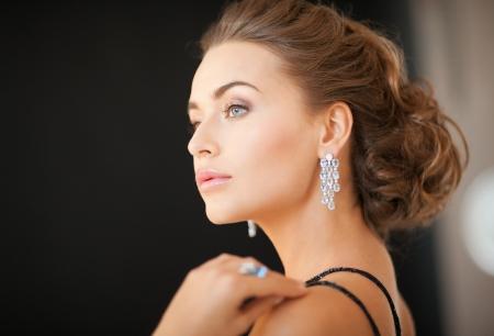aretes: hermosa mujer en traje de noche con aretes de diamantes