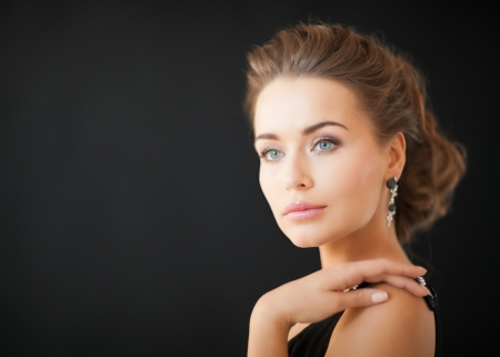 privilege: beautiful woman in evening dress wearing diamond earrings