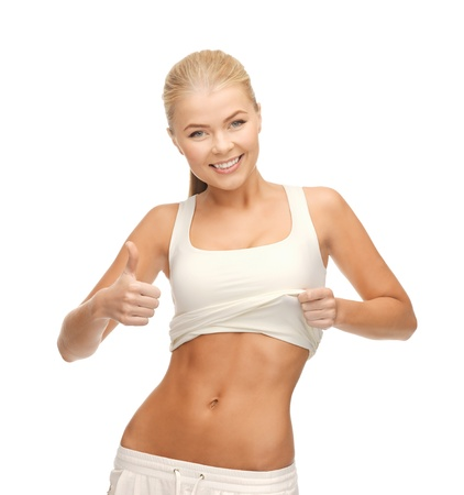 six pack: beautiful sporty woman showing thumbs up and her abs