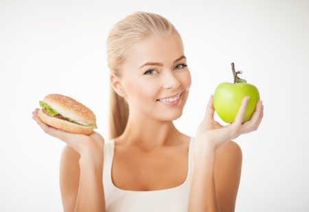 carbohydrates food: picture of sporty woman with apple and hamburger