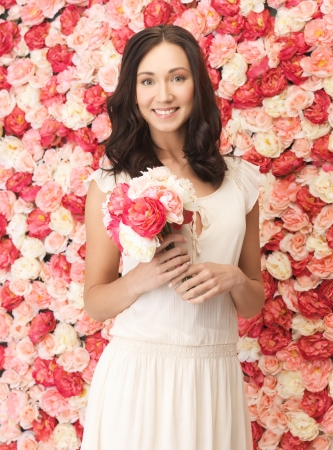 woman with bouquet of flowers and background full of roses Stock Photo - 19347261