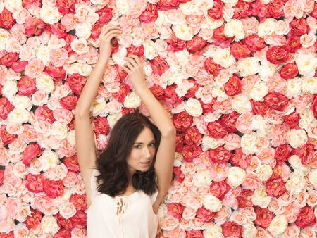beautiful and young woman with background full of roses Stock Photo - 19347297
