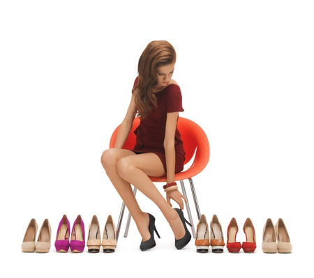 overspending: picture of sitting woman trying on high heeled shoes Stock Photo