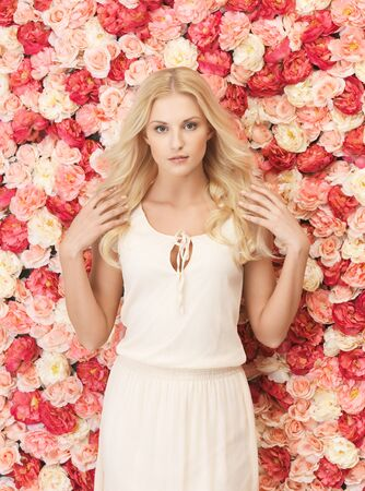 beautiful and young woman with  background full of roses  Stock Photo - 19347266