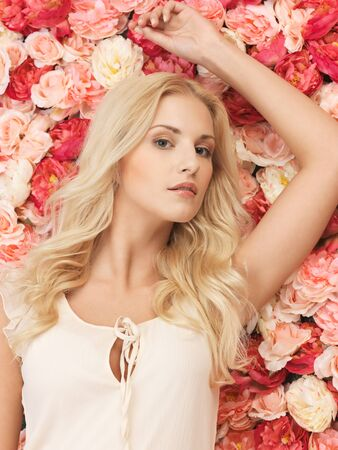 beautiful and young woman with background full of roses Stock Photo - 19347305