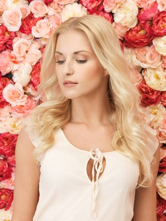beautiful and young woman with  background full of roses Stock Photo - 19347302