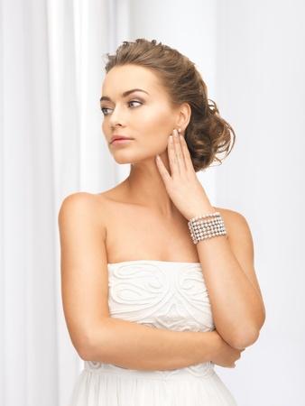 beautiful woman wearing pearl earrings and bracelet photo