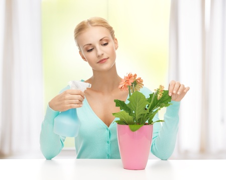 indoor plants: young woman holding pot with flower and spray bottle