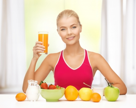 young woman with healthy breakfast and holding orange juice photo
