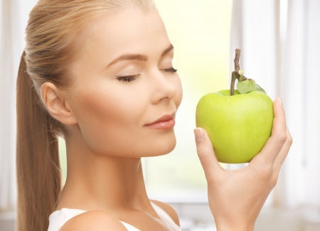 beautiful young woman smelling fresh green apple photo