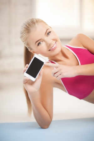 six pack abs: woman lying on the floor and sowing smartphone Stock Photo