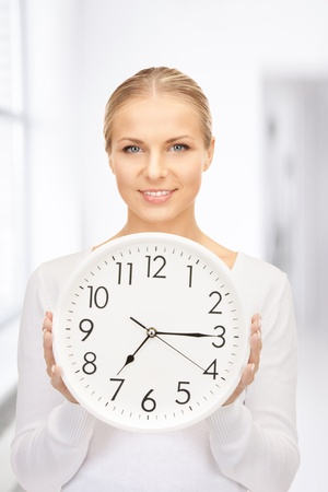 oclock: picture of woman holding big clock in office
