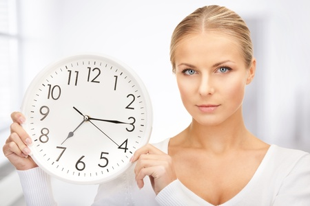 seven o'clock: picture of woman holding big clock in office