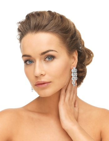 close-up of beautiful woman wearing shiny diamond earrings photo