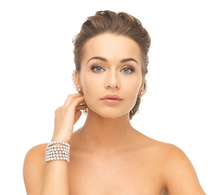 string of pearls: beautiful woman wearing pearl earrings and bracelet Stock Photo