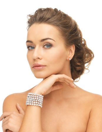 jewel hands: beautiful woman wearing pearl earrings and bracelet Stock Photo