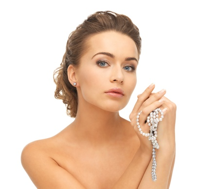 string of pearls: beautiful woman wearing pearl earrings and necklace Stock Photo