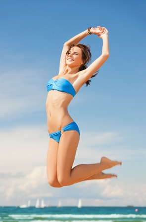 picture of beautiful woman in bikini jumping photo