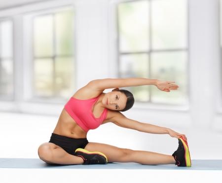 протяжение: Красивая спортивный женщина делает упражнения на полу