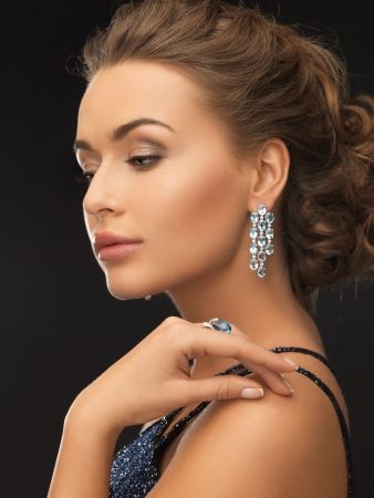 black dress: woman in evening dress wearing diamond earrings and ring Stock Photo