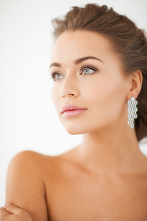 fashion jewelry: close up of beautiful woman wearing shiny diamond earrings