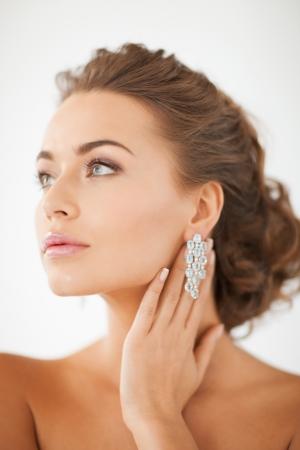 earrings: close up of beautiful woman wearing shiny diamond earrings