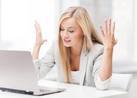 persona confundida: Foto de empresaria enojada con el ordenador portátil en el trabajo