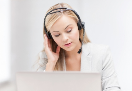 concerned: female helpline operator with headphones and laptop